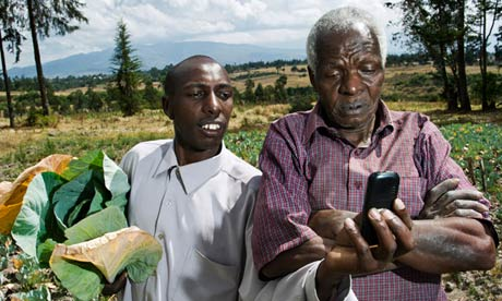 John Wahngombe, left, a farmer in North Kinangop, central Kenya, uses the M-Farm app to check crop prices.